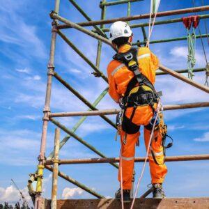 lavoratore edile che indossa cinture di sicurezza durante l'allestimento e lavoro su ponteggi