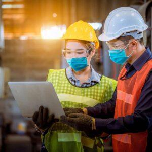 Donna lavoratrice e ingegnere durante ispezione e controllo del processo di produzione che indossano elemtto di sicurezza e maschera di sicurezza per proteggersi da inquinamento in fabbrica