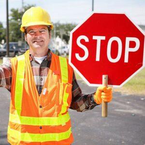 Operaio edile sulla strada che regge un cartello di stop