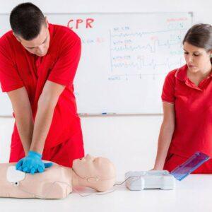 Operatori sanitari che fanno prove di massaggio cardiaco su manichino