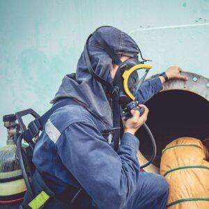 Operaio con tuta e maschera che ispeziona tubatura nell'ambito di spazi confinati